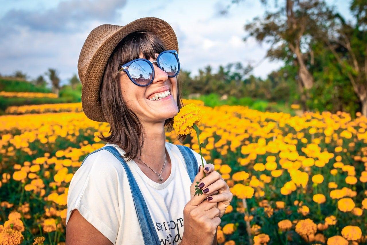 Mulher de chapéu e óculos de sol sorrindo no foco com flor na mão e campo cheio de flores ao fundo
