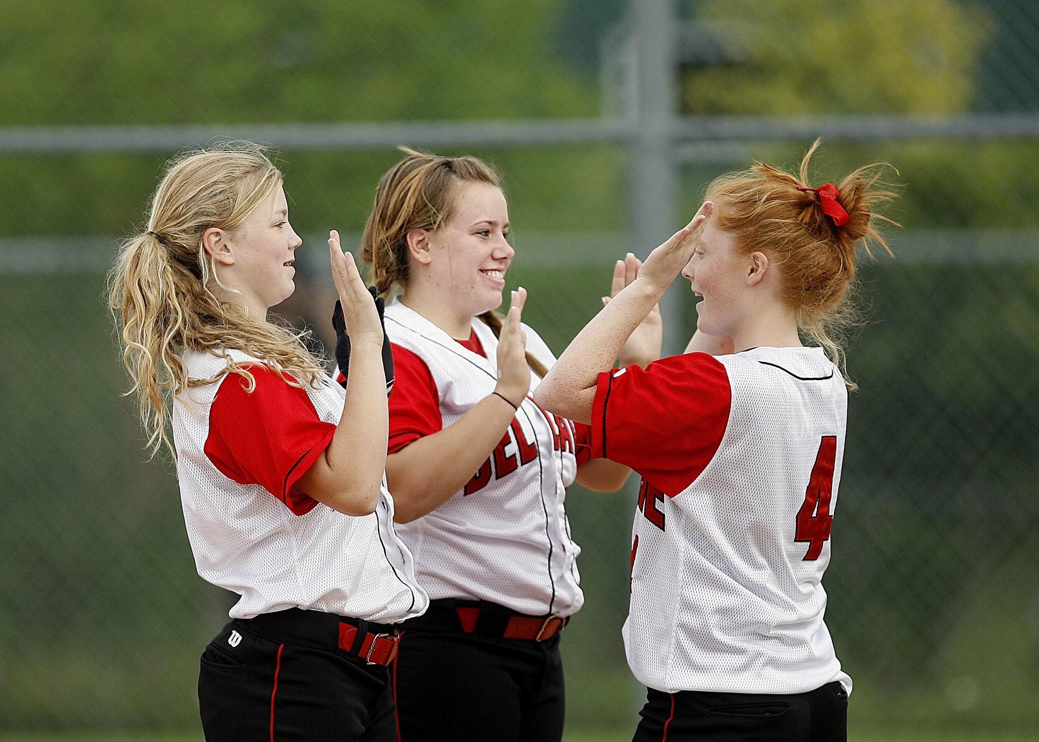 """Três jovens com uniforme de esporte e cabelos presos tocam as mãos umas das outras com um """"high five""""."""