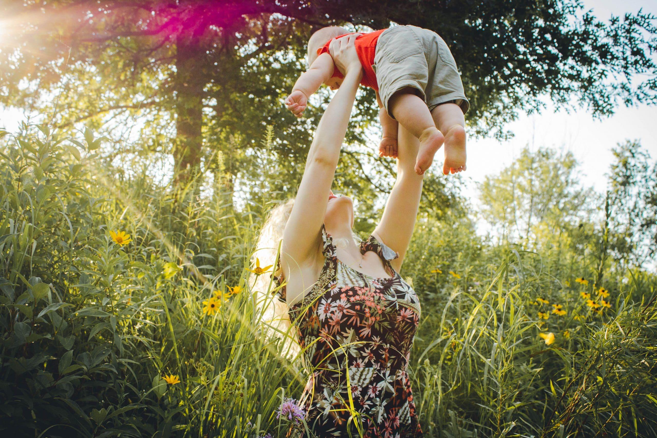 Mãe levanta o filho nos braços em um jardim ensolarado.