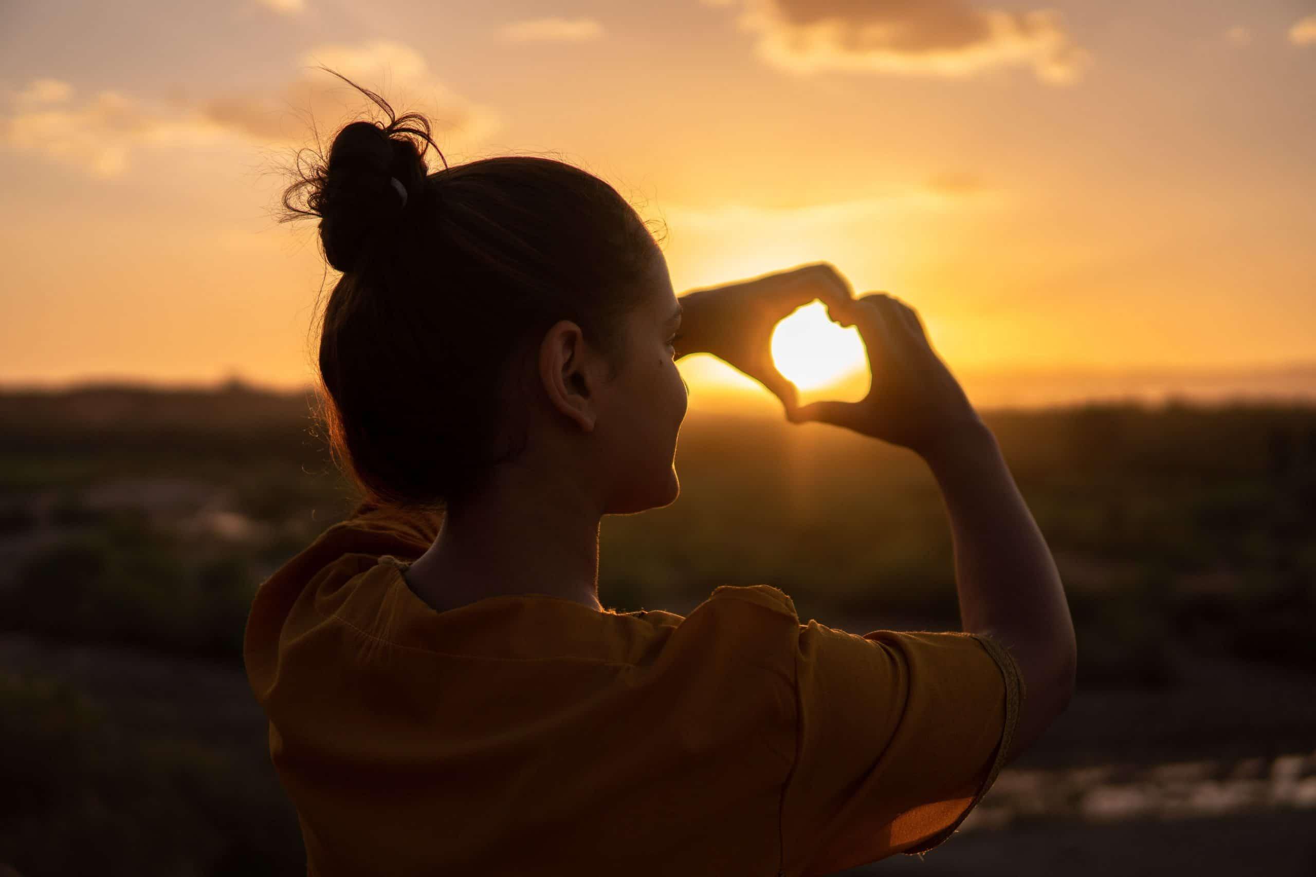Mulher de costas, com os cabelos presos, fazendo um coração que aponta para o pôr-do-sol no horizonte com as duas mãos.