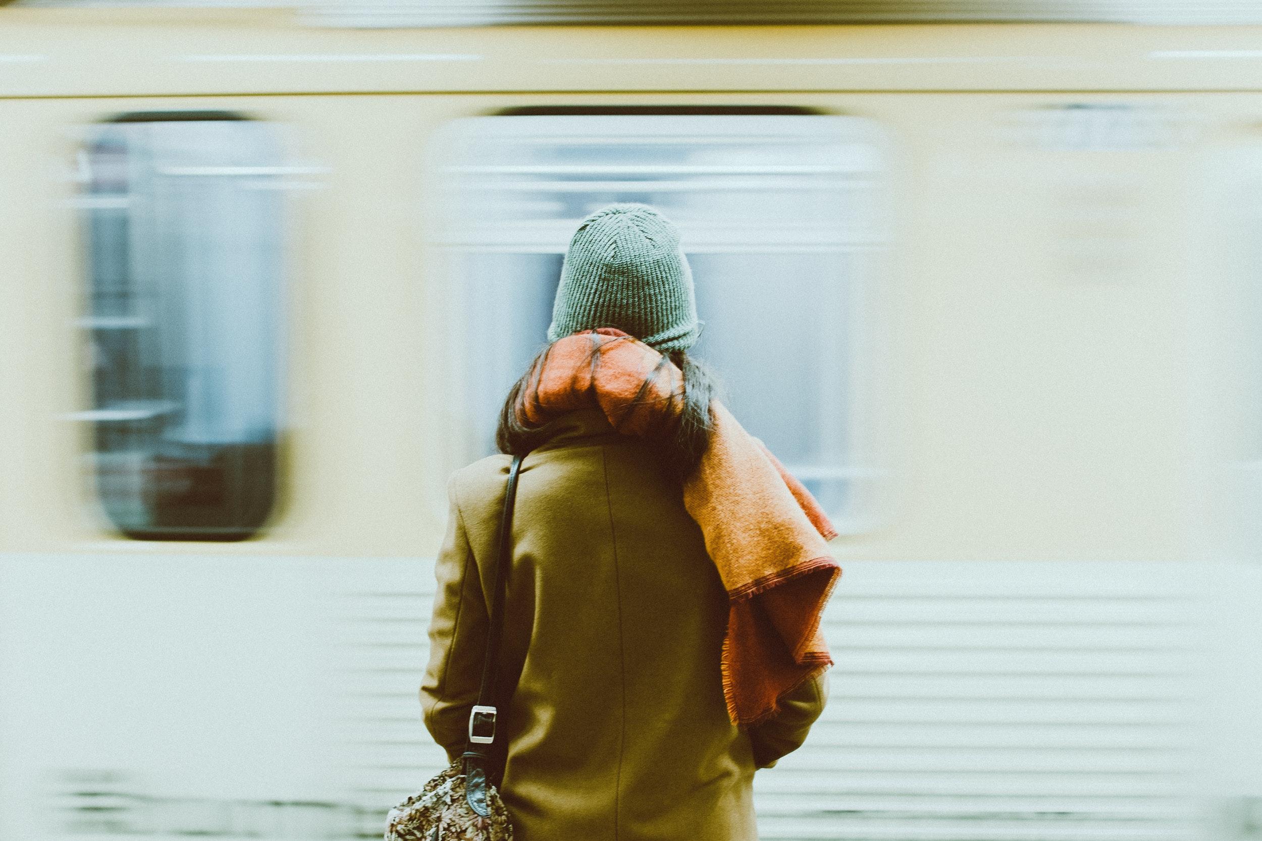 Pessoa com roupas de frio, de costas, observando o metrô que passa com velocidade.