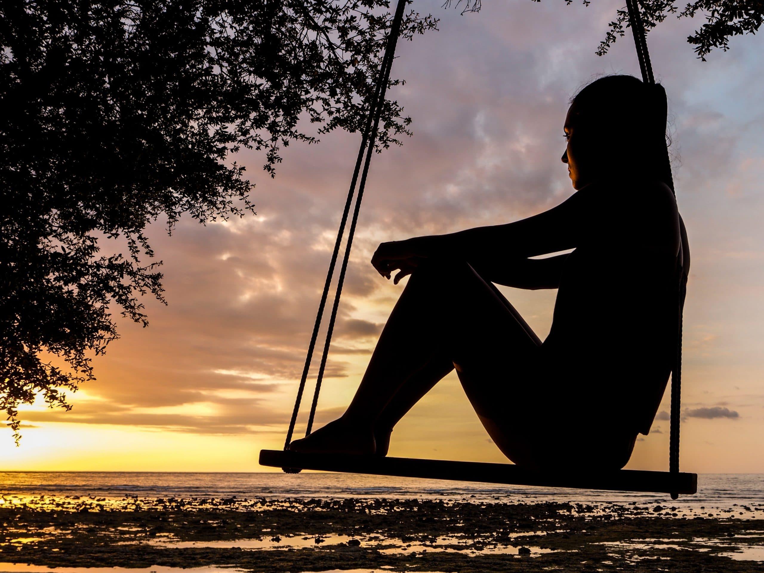 Mulher sentada sobre um balanço em uma árvore olhando a paisagem. Ela está com as costas encostadas em uma das cordas, os joelhos dobrados sob os braços em repouso. No horizonte, há o mar e o pôr-do-sol.