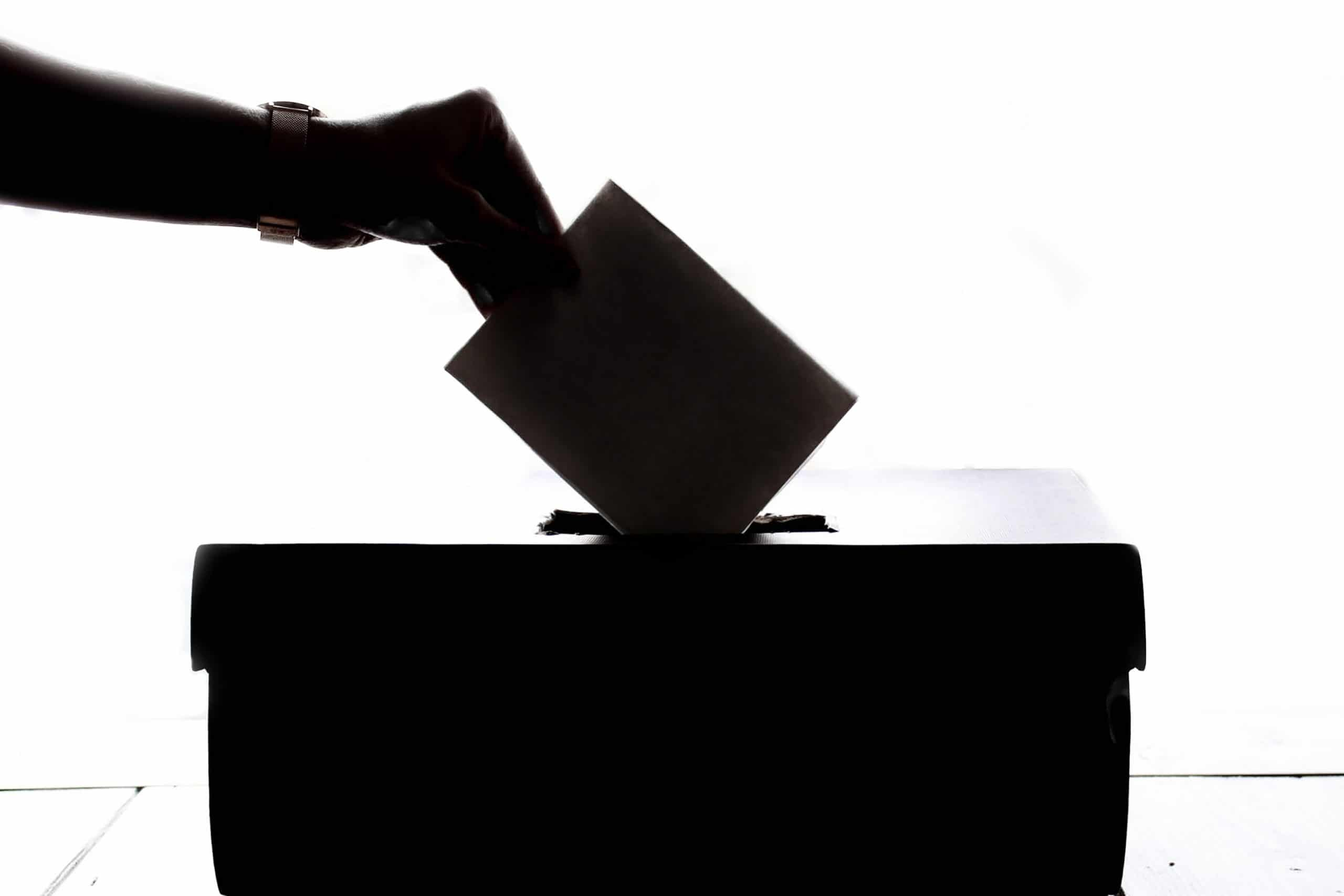 Pessoa depositando seu voto na urna. A mão, o voto e a urna estão na sombra, enquanto o foco de luz da imagem vem do fundo.