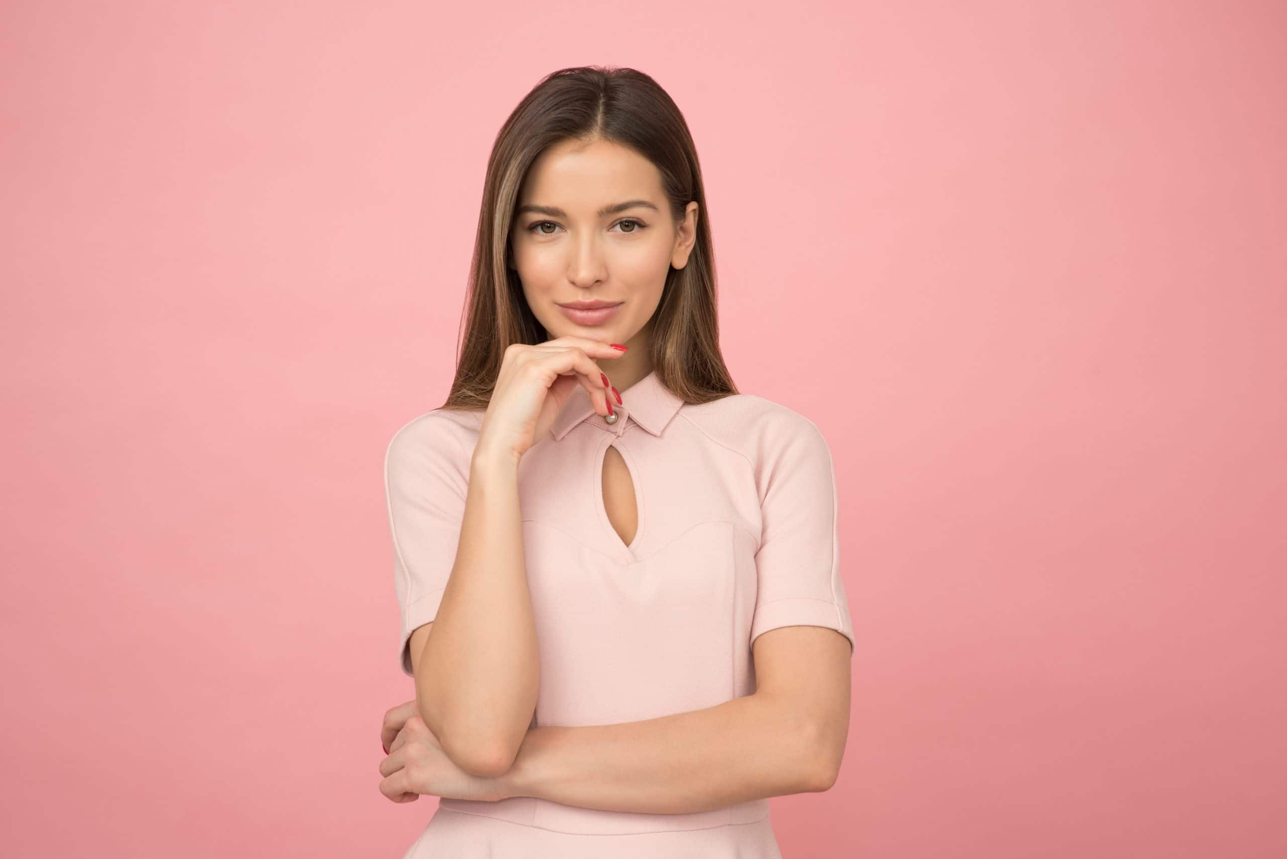 Mulher com uma roupa rosa claro, com um dos braços à frente do seu corpo e outro apoiado nele, segurando o queixo e sorrindo levemente. Ela está em frente a uma parede rosa.