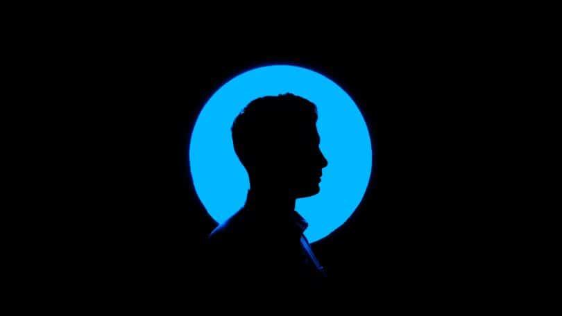Silhuete de um homem de perfil em frente a uma fonte circular de luz azul sobre um fundo preto.