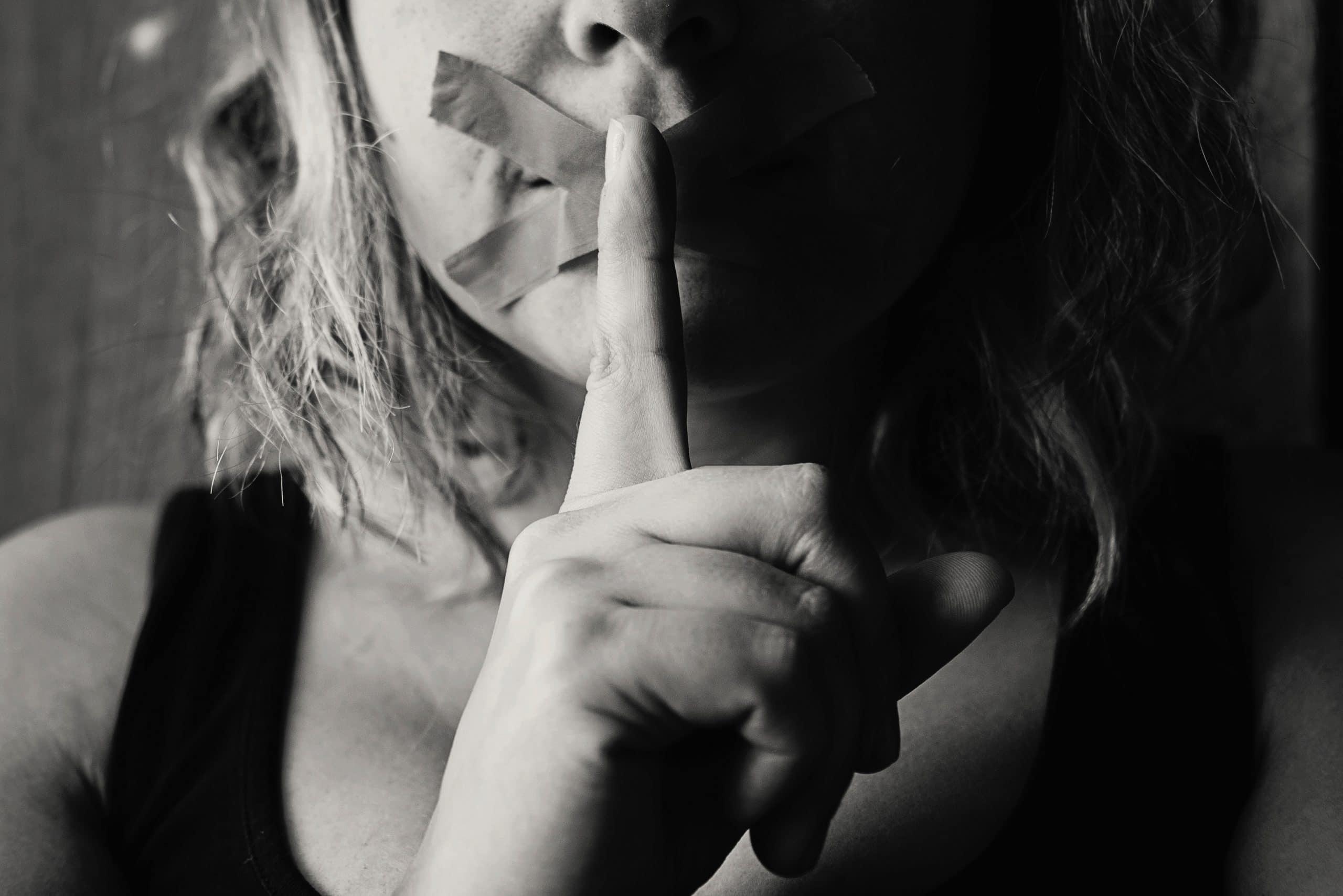Mulher com uma fita em X sobre a boca, com o dedo indicador levantado na frente do rosto, em sinal de um pedido de silêncio.