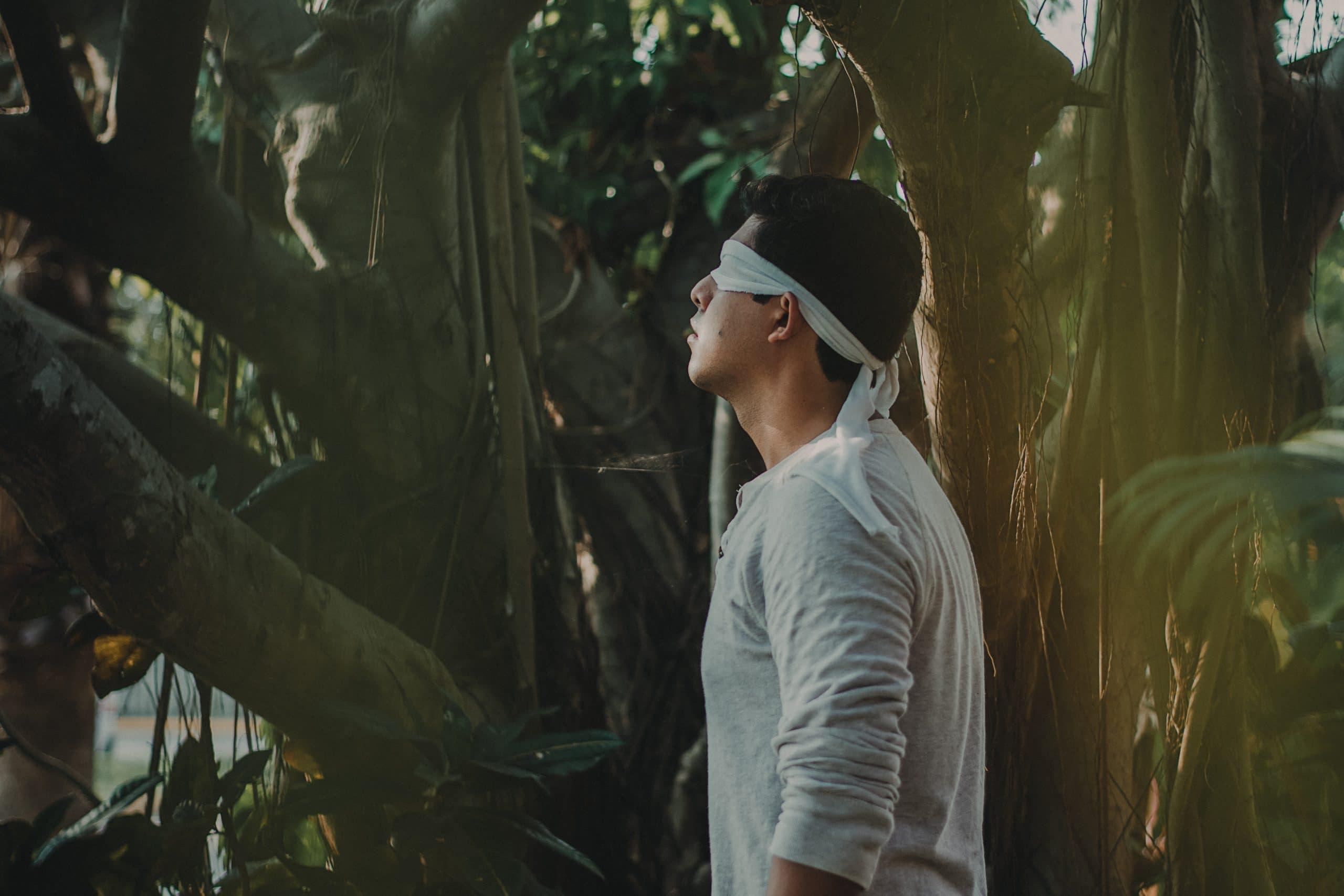 Homem com uma venda branca nos olhos tentando se encontrar em meio a selva.