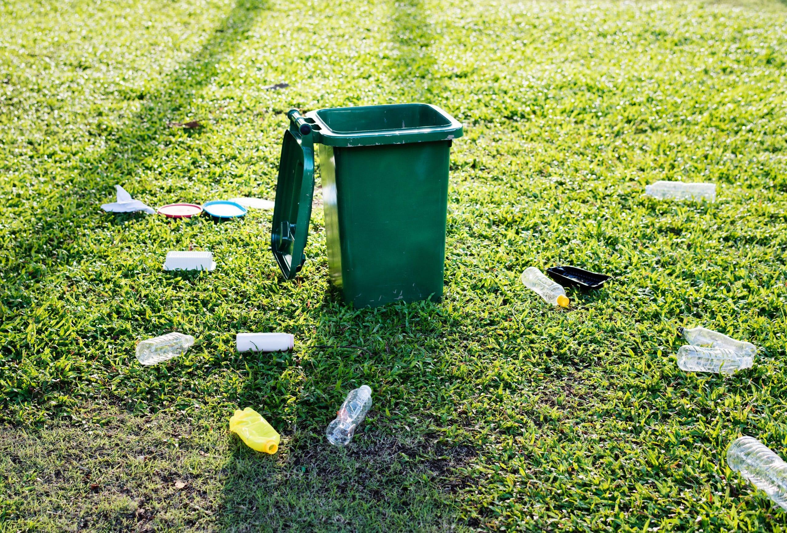 Várias garrafas de plástico espalhadas por um gramado ao redor de uma lixeira aberta.