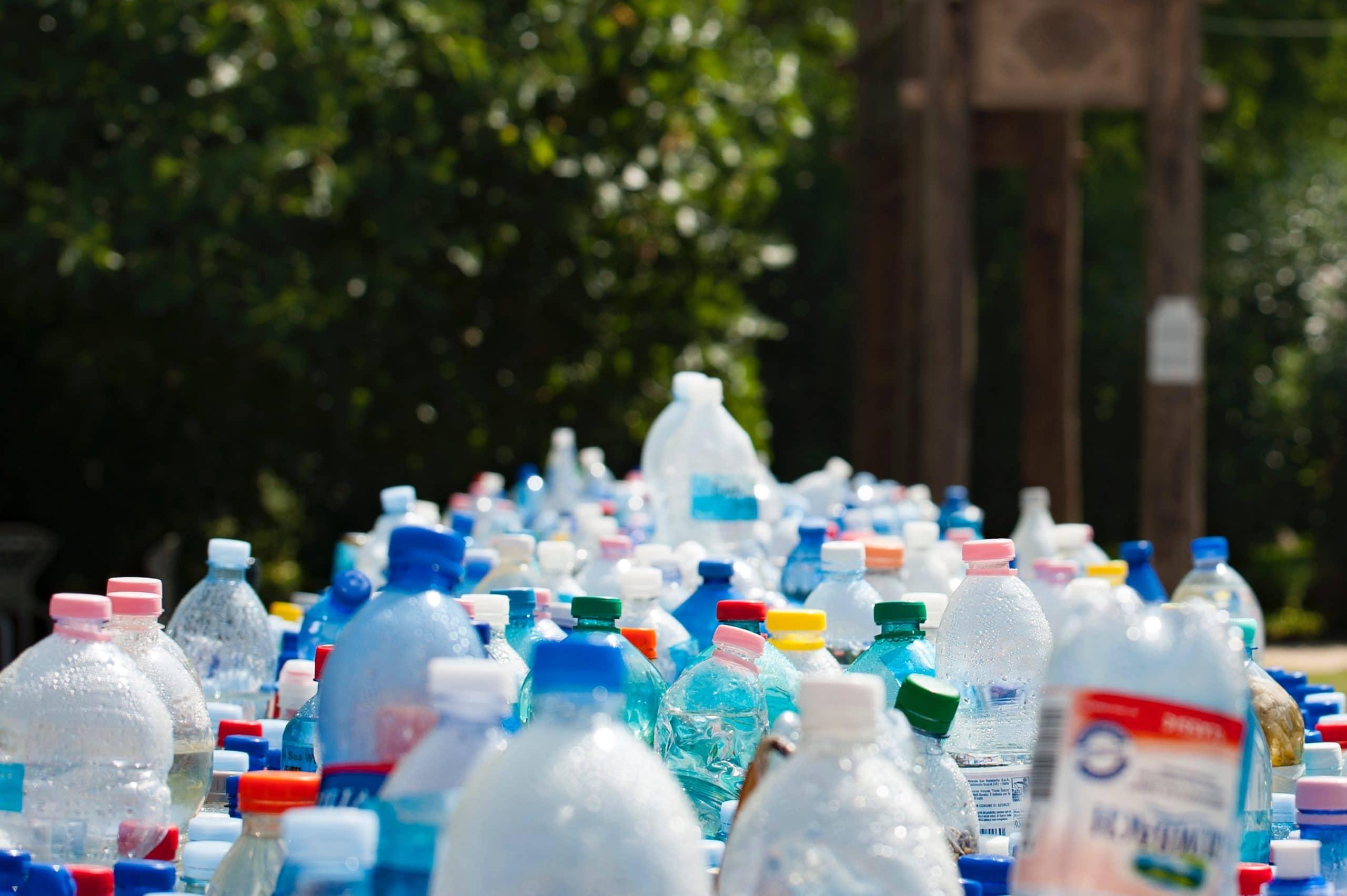 Amontoado de garrafas de plástico na frente de um fundo com árvores e natureza.