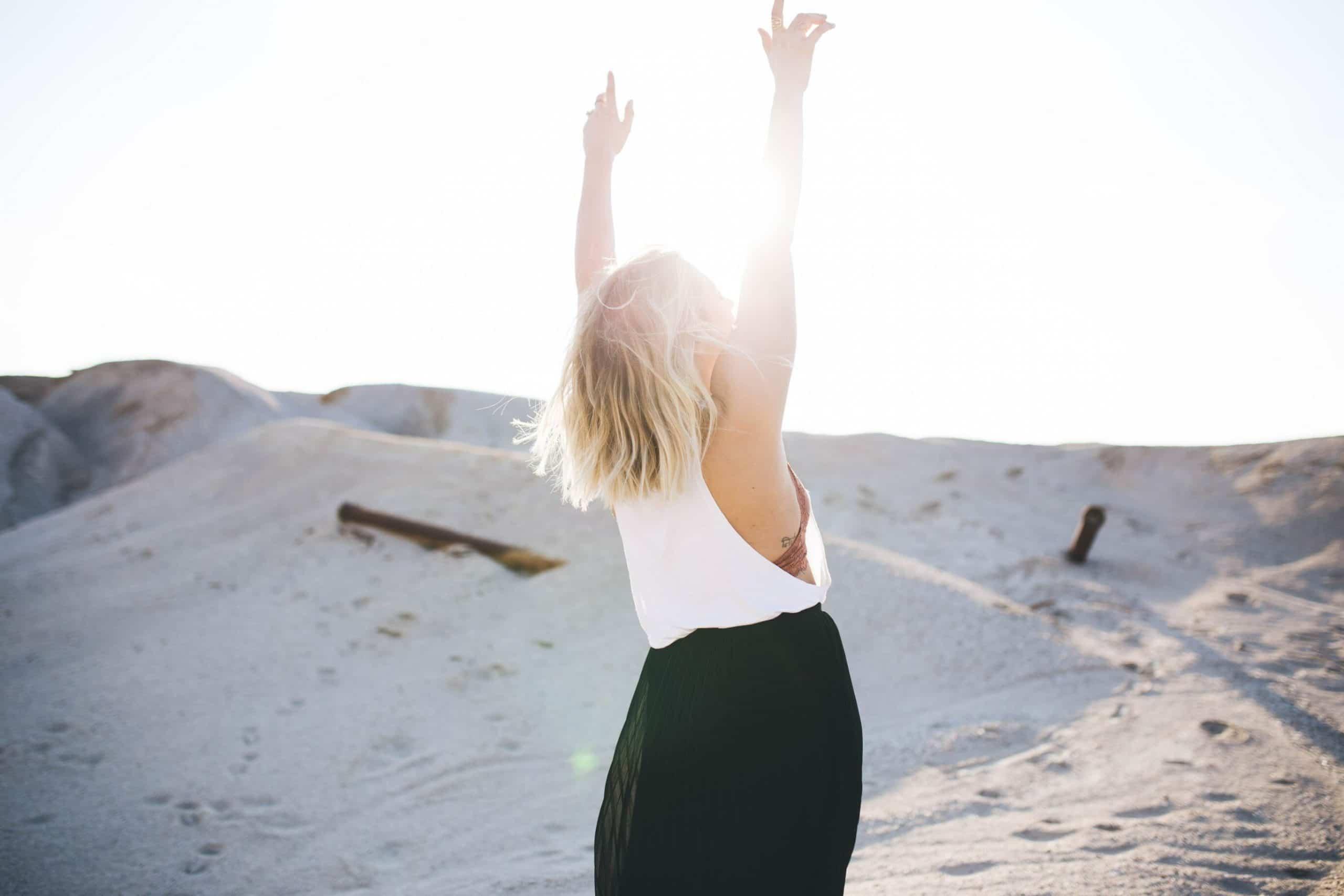 Mulher loira de cabelos curtos de costas com braçoes para o alto com areia branca no fundo e sol refletindo