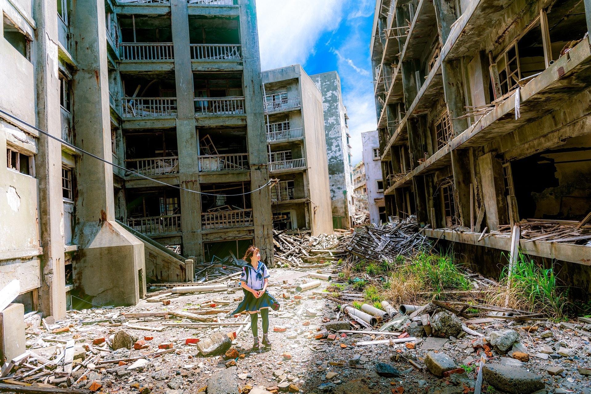 Menina parada em meio a prédios destruídos e caindo aos pedaços após catástrofe.