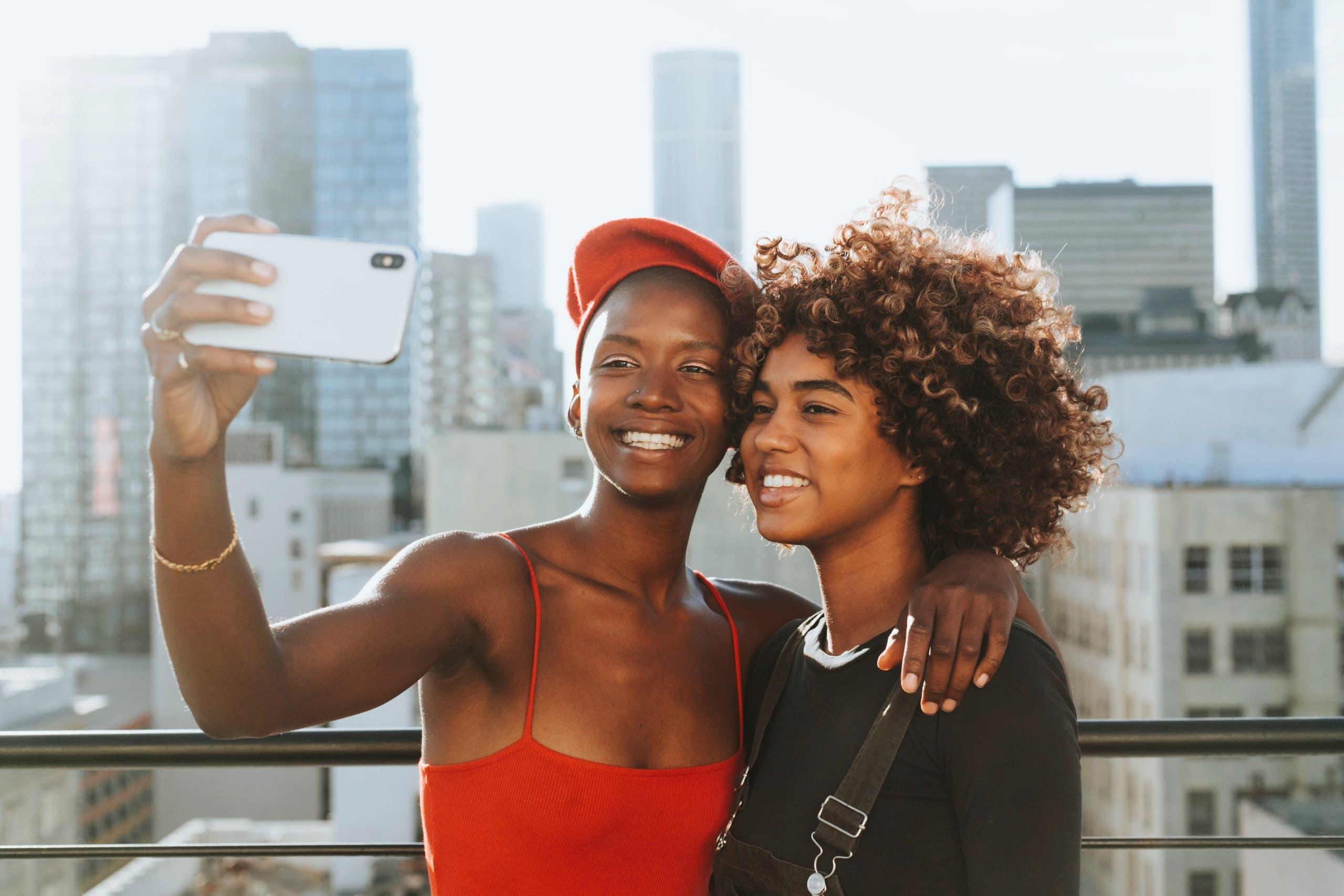 Duas jovens se abraçam e tiram uma selfie sorrindo, com a cidade ao fundo.