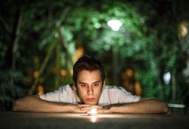 Homem branco, apoiando-se em uma mesa, observando uma pedra luminosa, com plantas ao fundo.