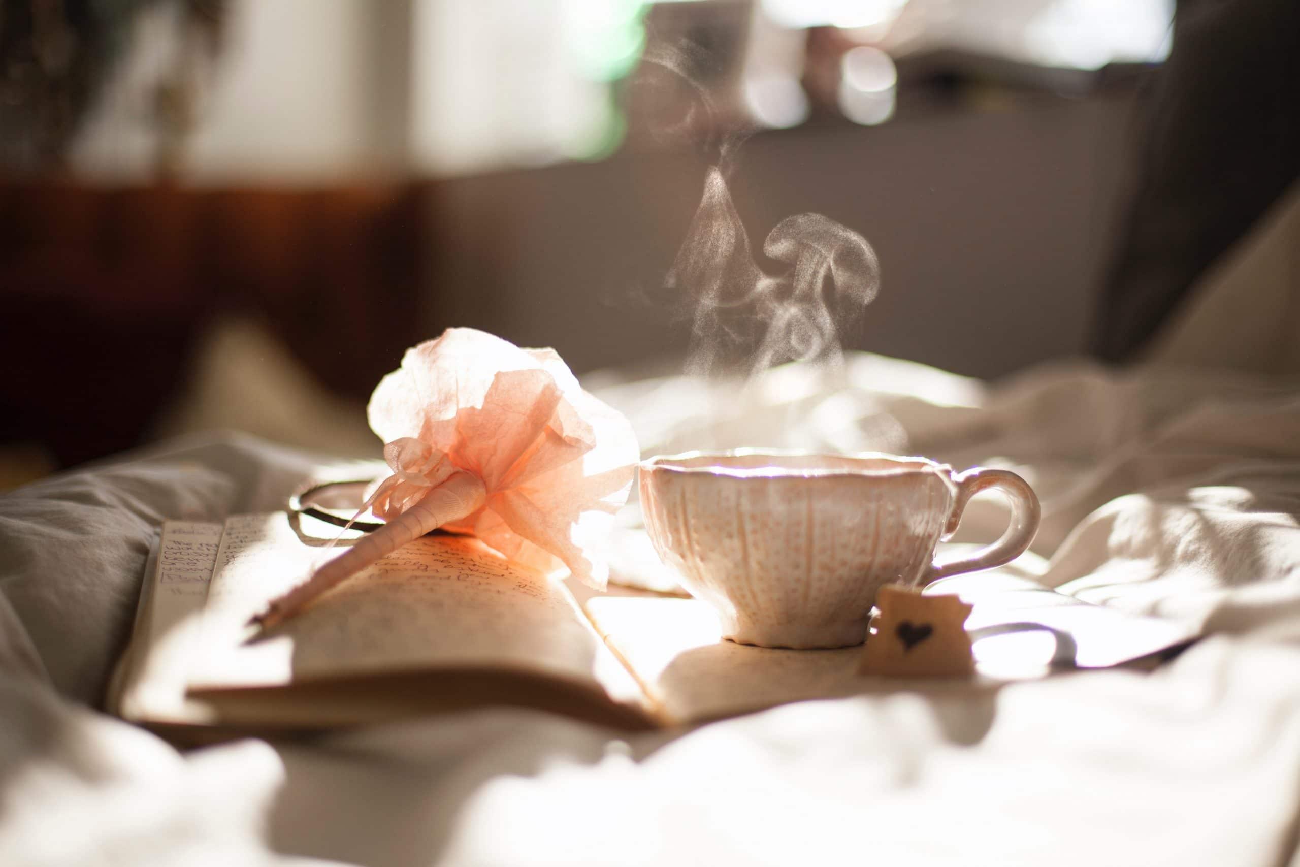 Um livro, uma caneta decorada em formato de flor e uma xícara de café com fumaça saindo posicionados em cima da cama bagunçada, com a luz do dia iluminando-os.