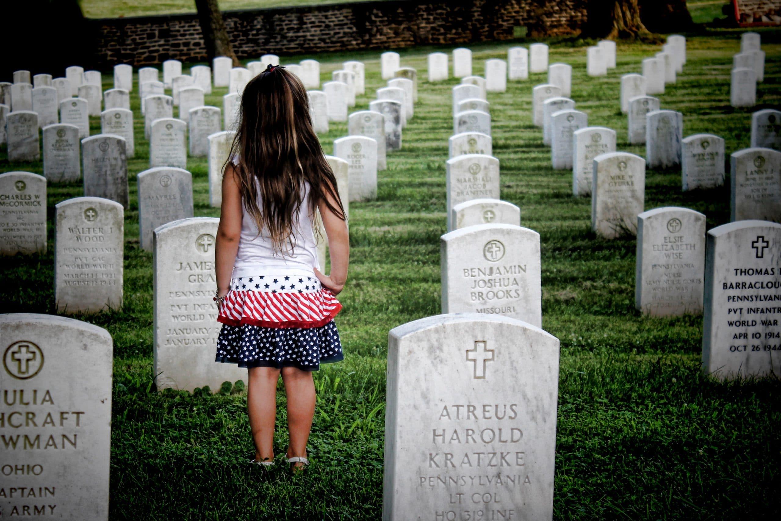 Menina em pé, de costas, entre várias lápides de um cemitério.
