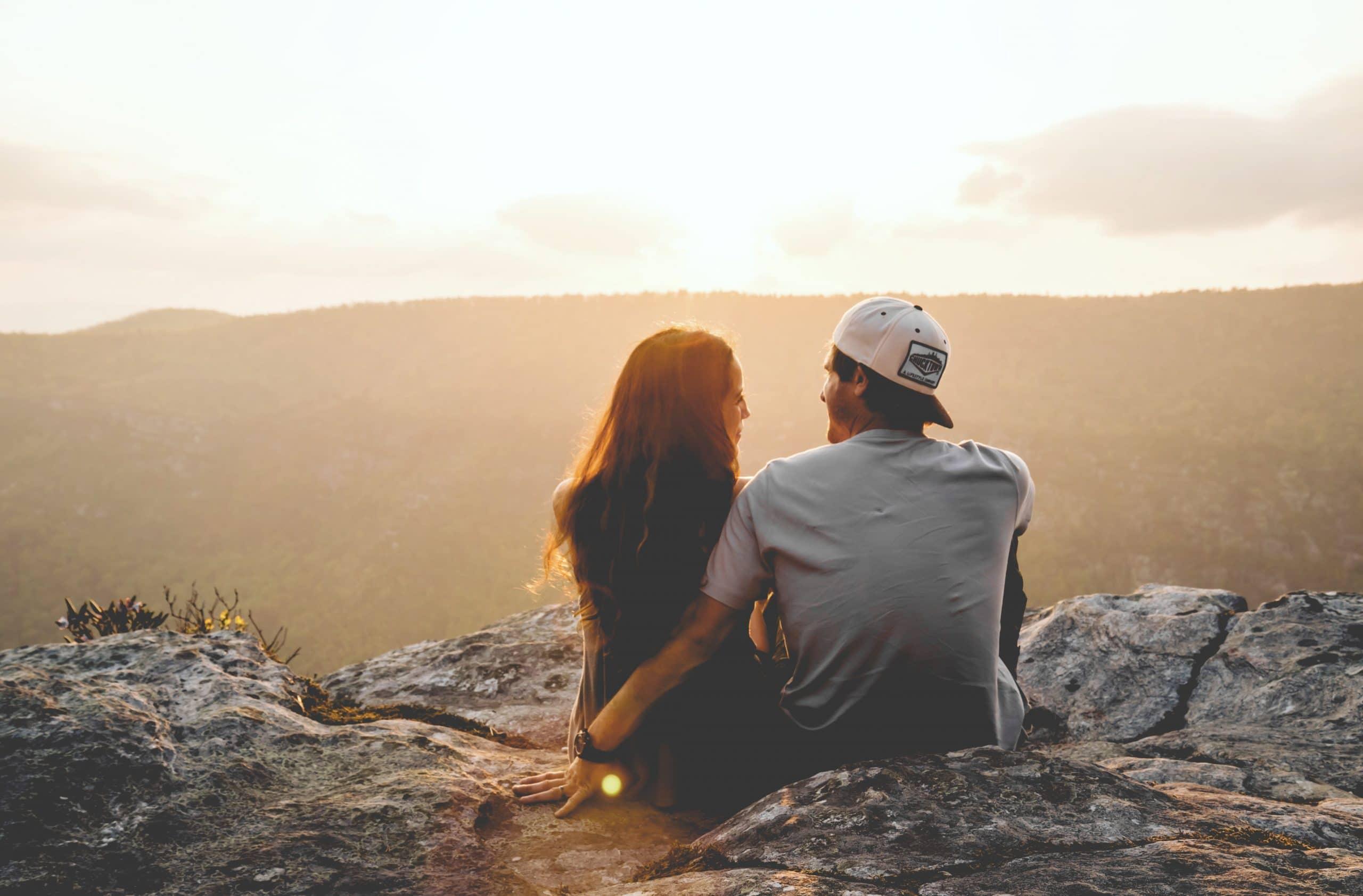 Casal de costas sentados em montanha com por-do-sol ao fundo