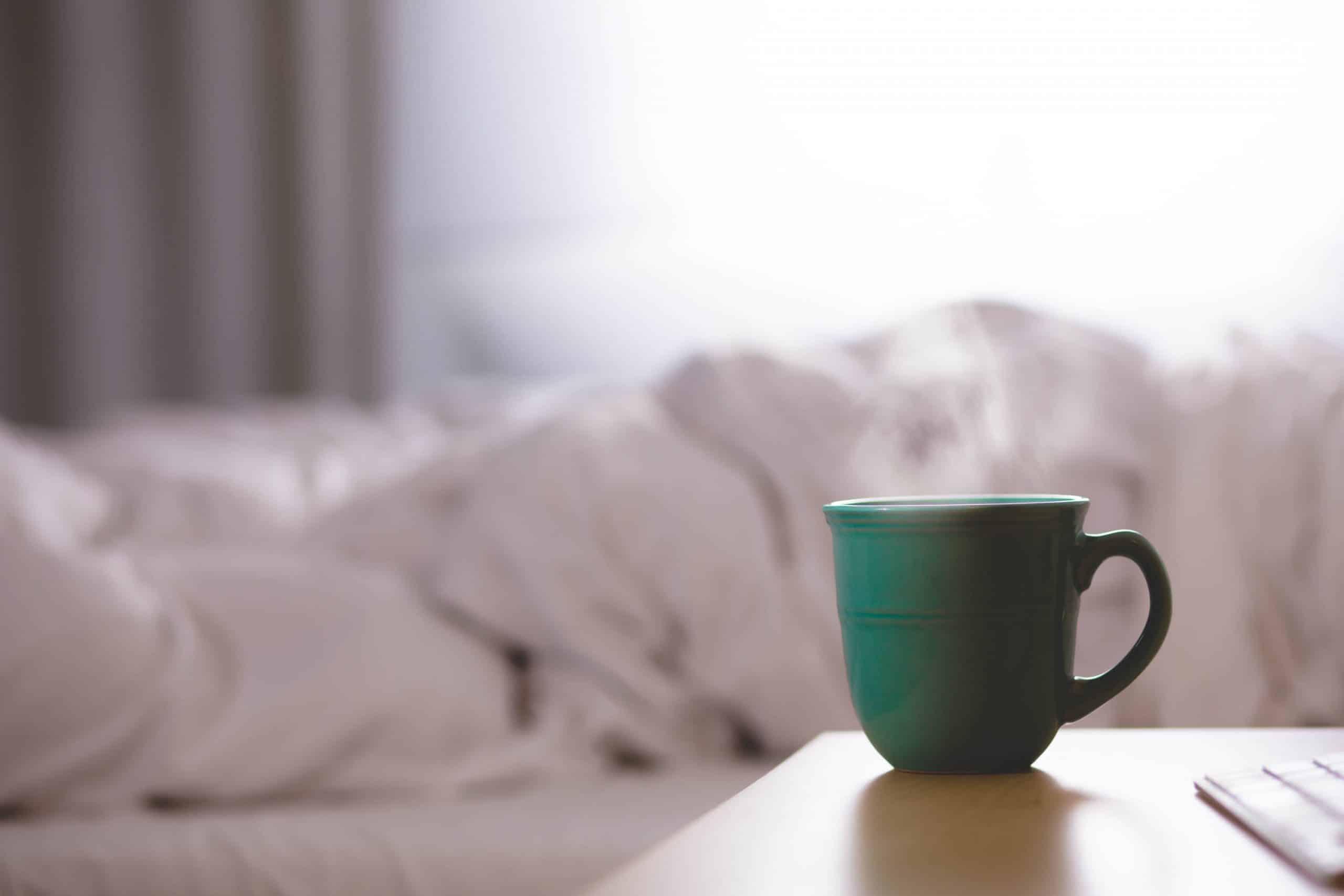 Xícara de café com fumaça saindo em cima de um criado-mudo. Ao fundo, uma cama bagunçada sendo iluminada pela luz do dia que entra no quarto.