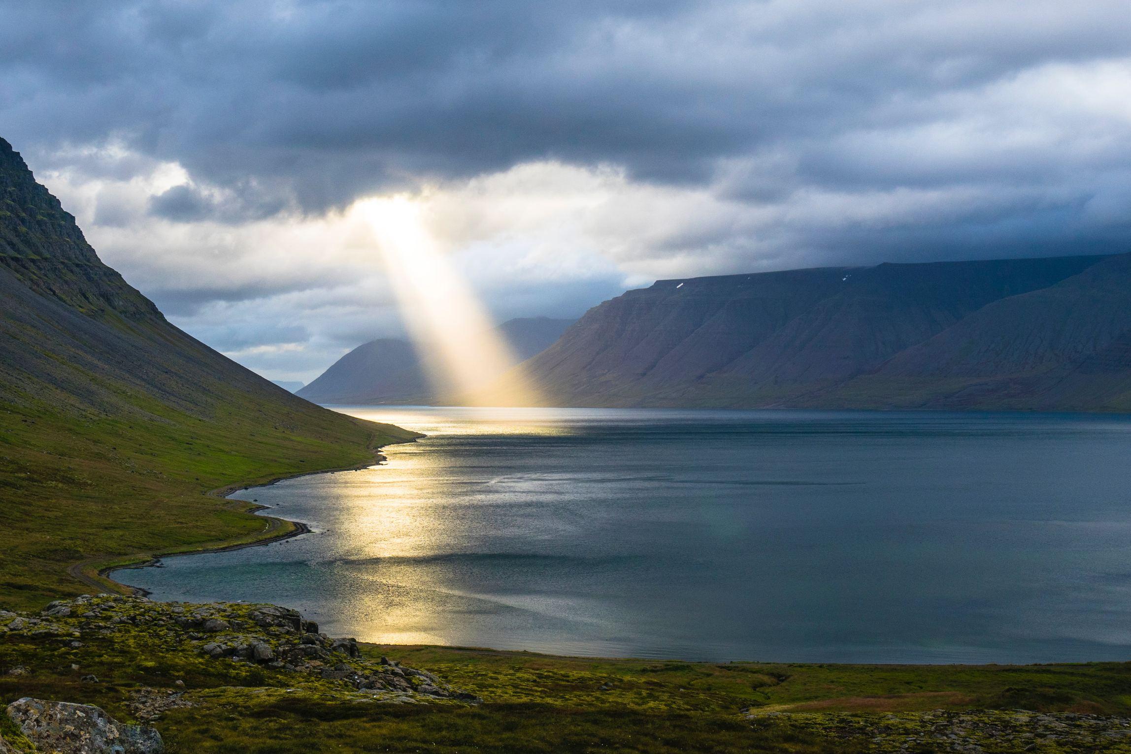 Paisagem de rio e campo com luz refletida do sol diretamente para o rio