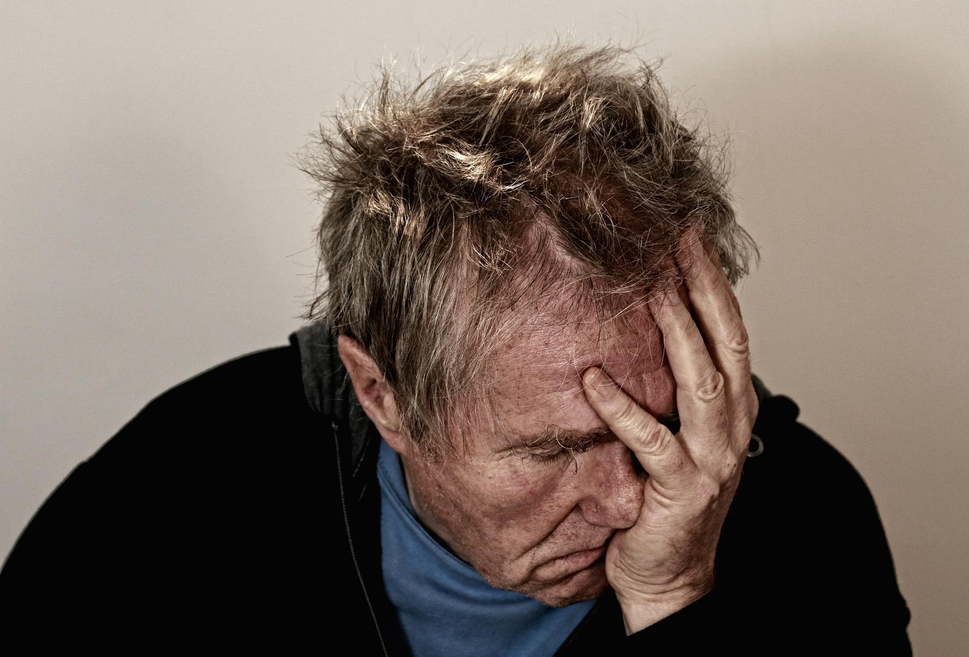 Homem de idade com a mão no rosto em sinal de dor e cansaço.