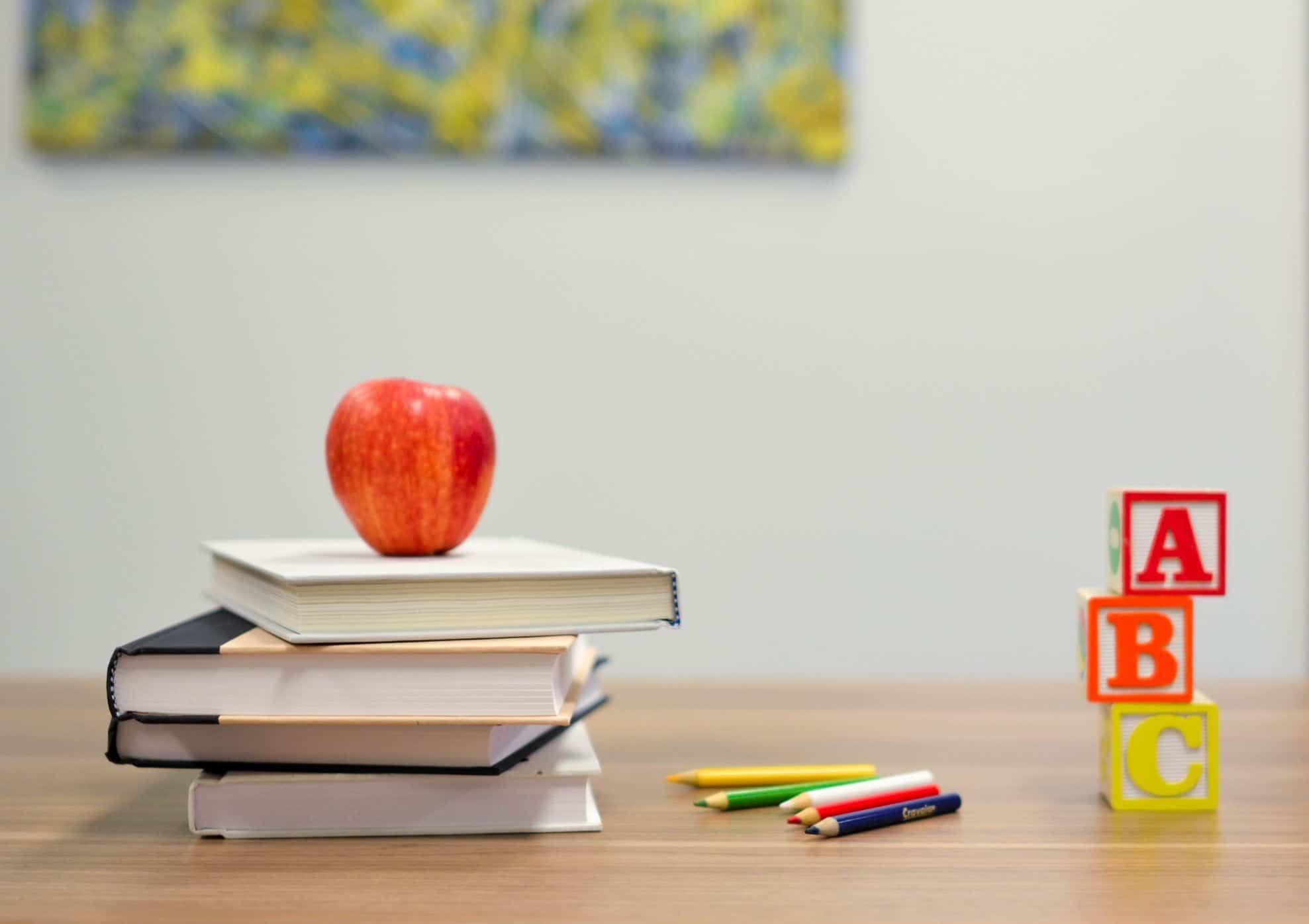 Mesa com livros e maçã em cima deles, lápis de cor e cubos coloridos com ABC