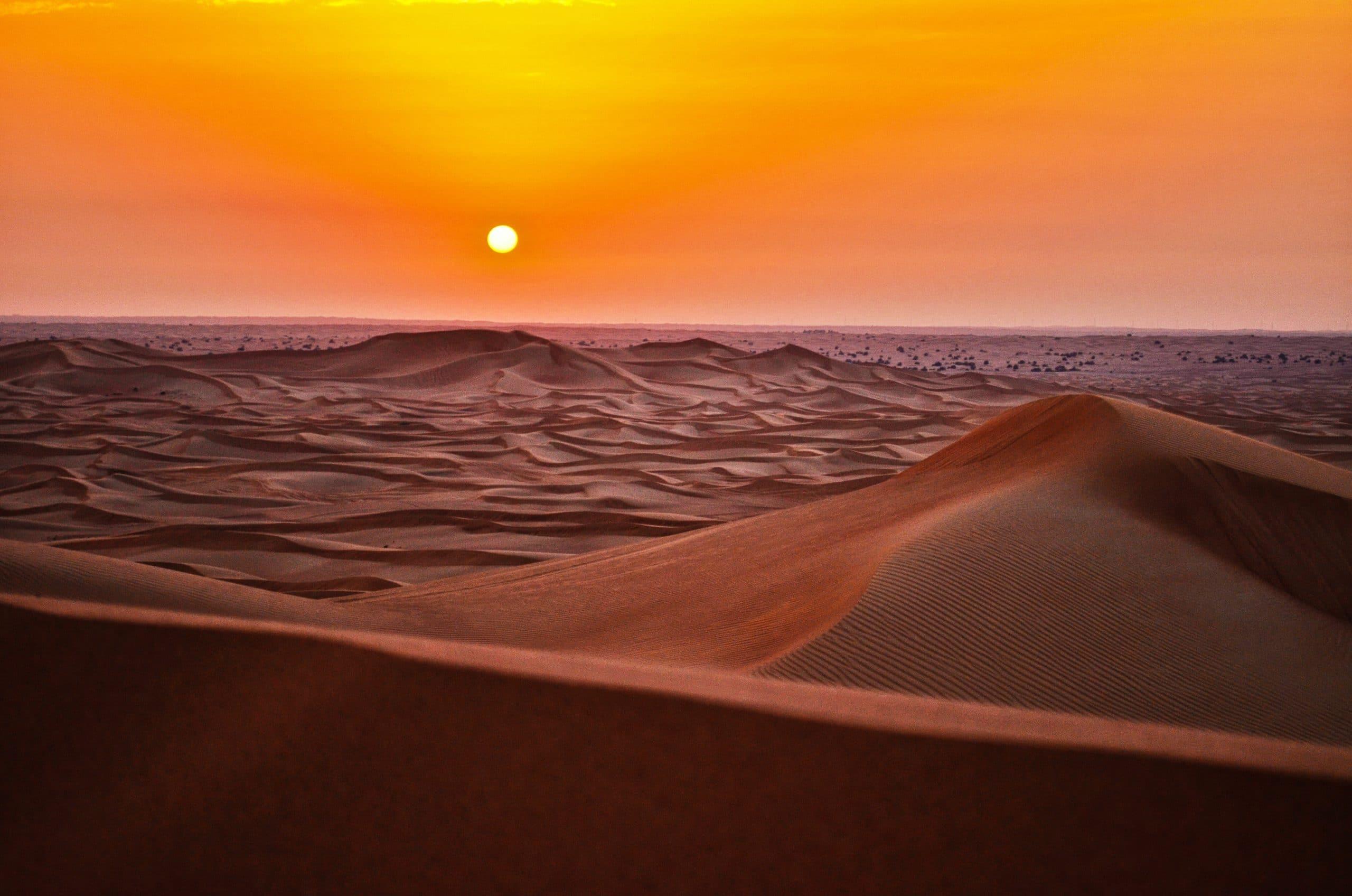 Grandes dunas no deserto recebendo luz e energia do Sol que está ao fundo, no horizonte.