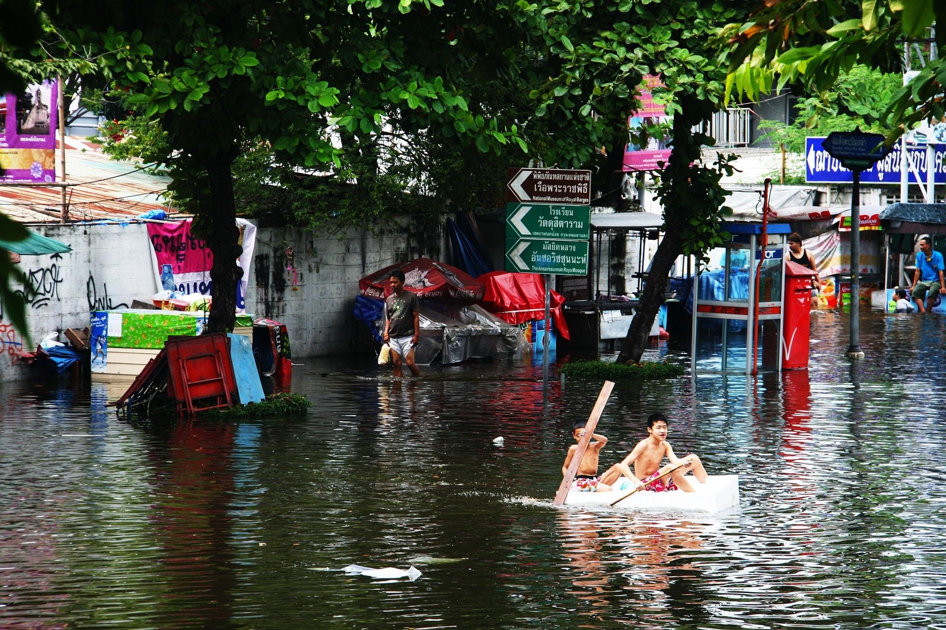 Cidade alagada após enchente. Muitos elementos das ruas estão quase submersos e duas crianças remam em meio à água em um barco improvisado.