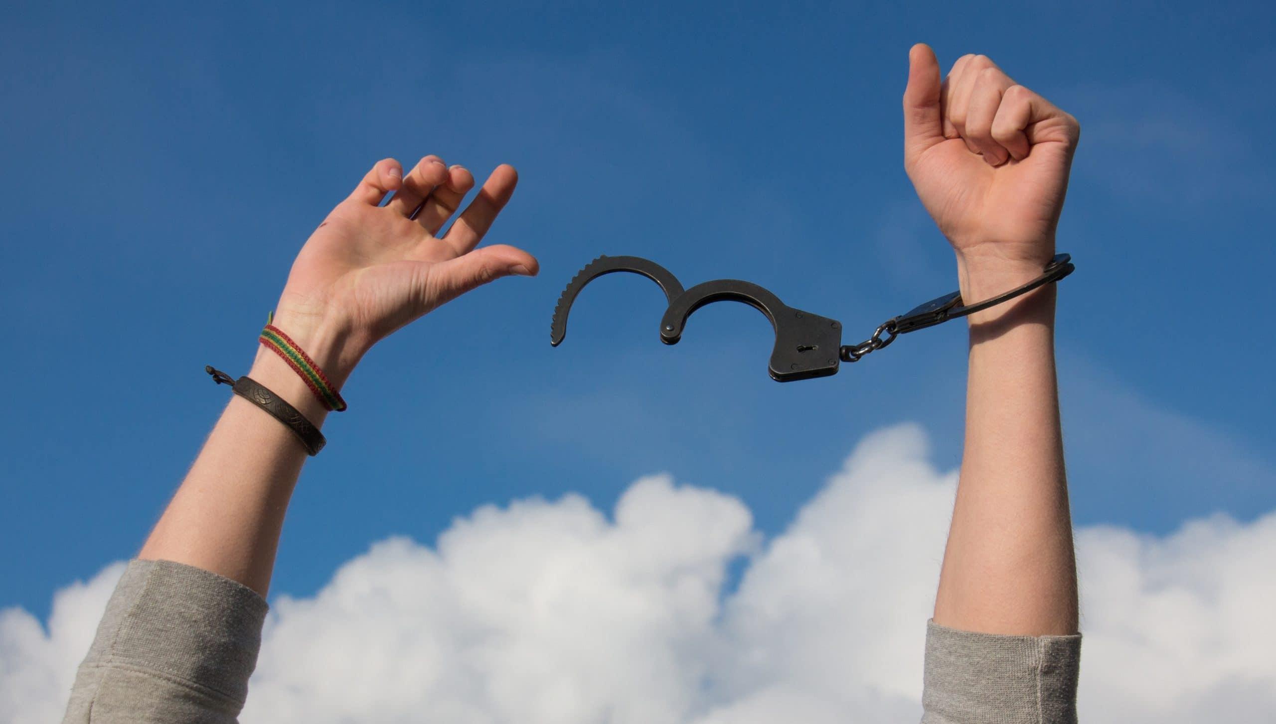 Mãos levantadas para o céu, libertando-se de algemas.