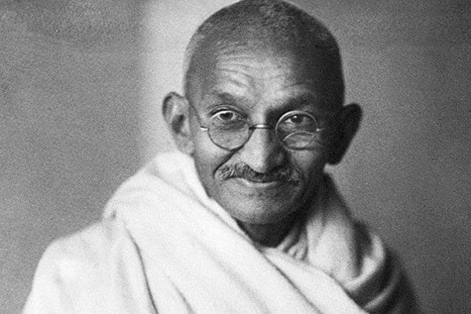 Ghandi sorrindo, vestindo seus trajes característicos e um óculos redondo.