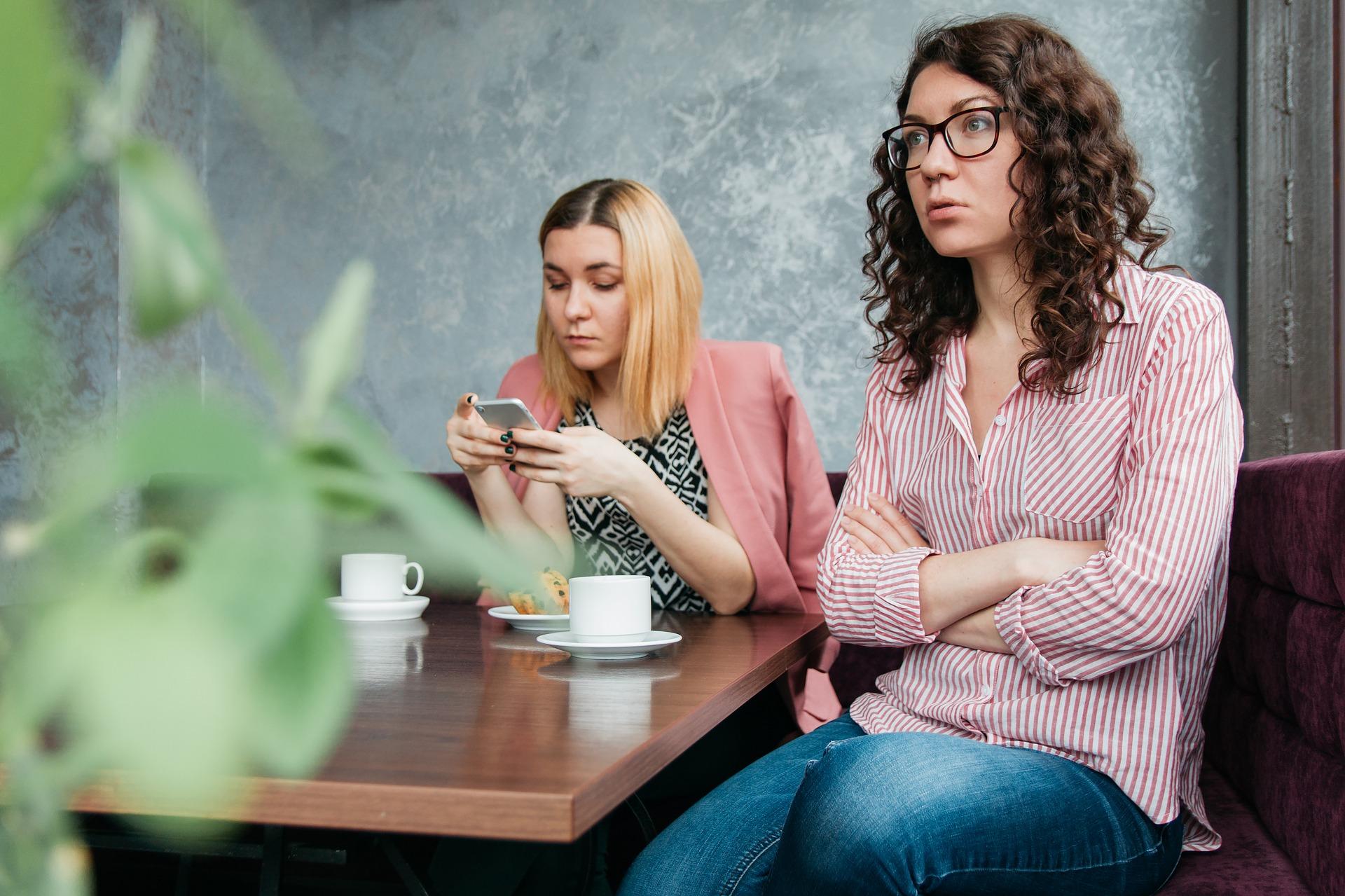 Duas mulheres sentadas a mesa tomando café. Uma delas mexe no celular com feição de indiferença. A outra olha para o lado oposto, com os braços cruzados, incomodada.