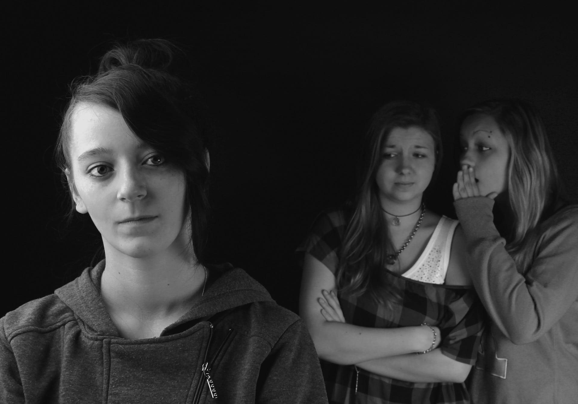 Duas meninas ao fundo fazem fofoca sobre outra garota, mais a frente. O rosto desta expressa desconforto, enquanto a das duas outras, estranhamento e superioridade.