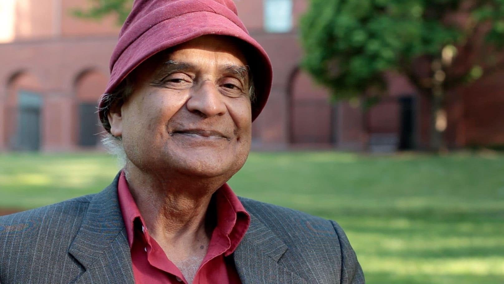 Amit Goswami sorrindo em frente ao jardim de uma universidade, vestindo camisa e chapéu vinhos, além de um terno preto.