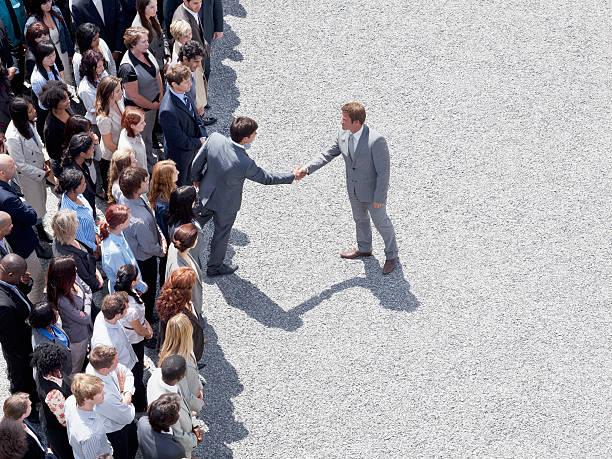 Homem sozinho, vestido de terno cumprimentando outro homem de terno, que esta cercado de pessoas.