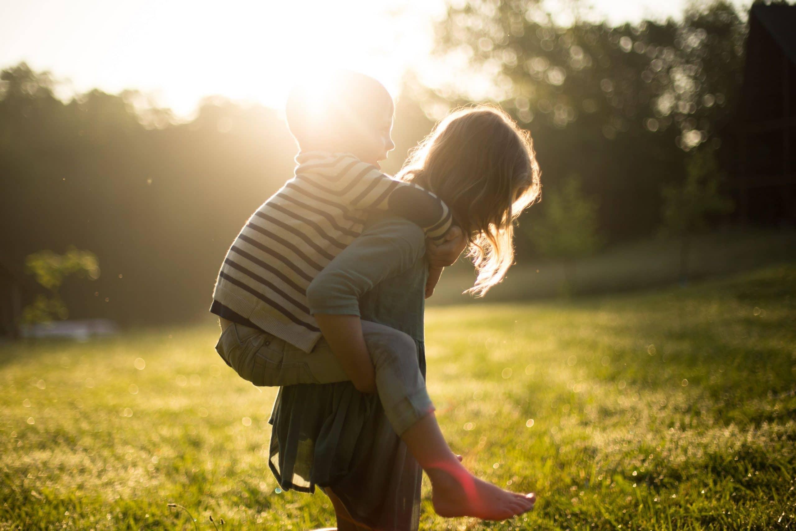 Mãe com filho nas costas com sol refletindo no fundo