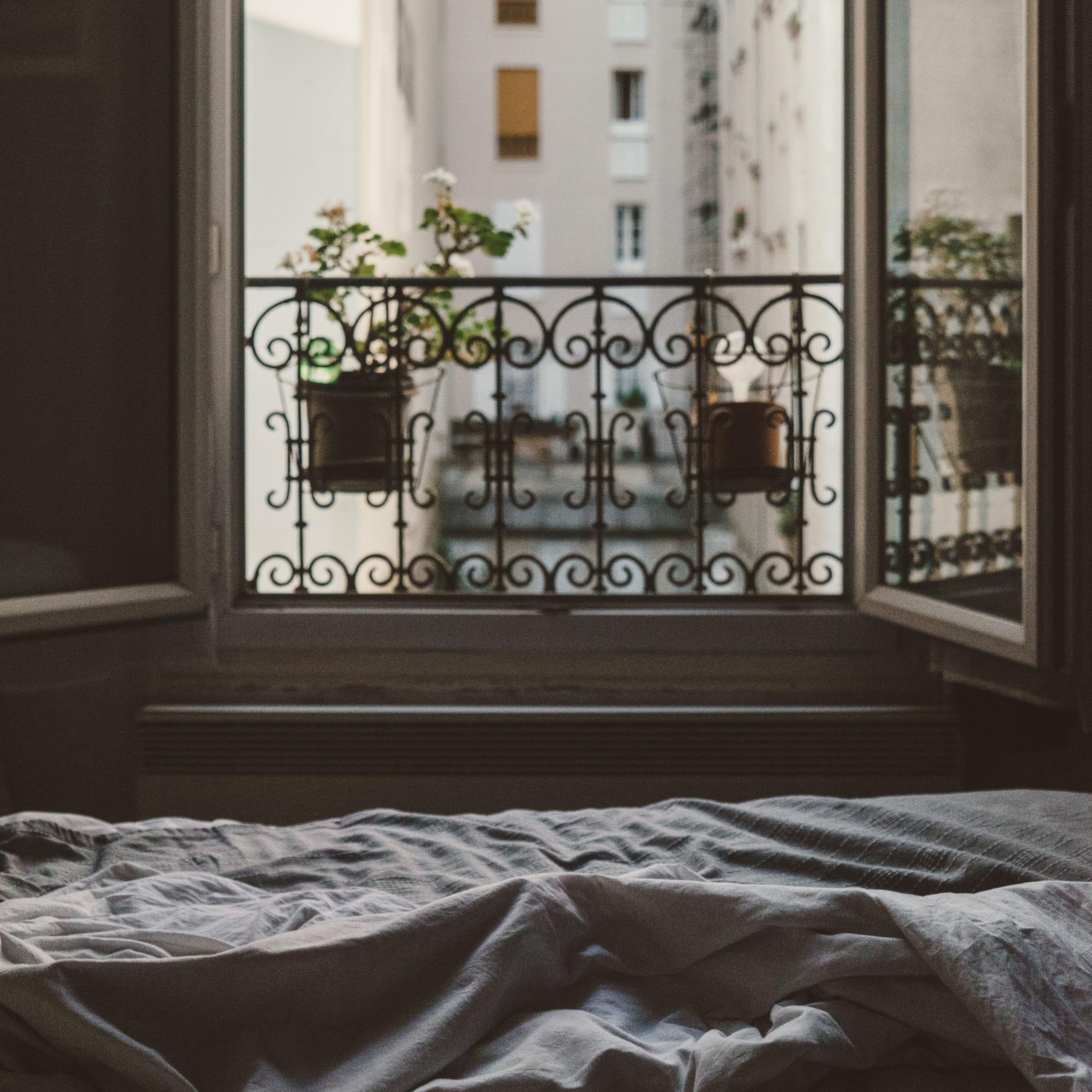 Luz da manhã entrando no quarto pela janela. No quarto, há uma cama com lençóis bagunçados. A janela possui grades decorativas e dois vasos de plantas. A visão da janela é a de um prédio.
