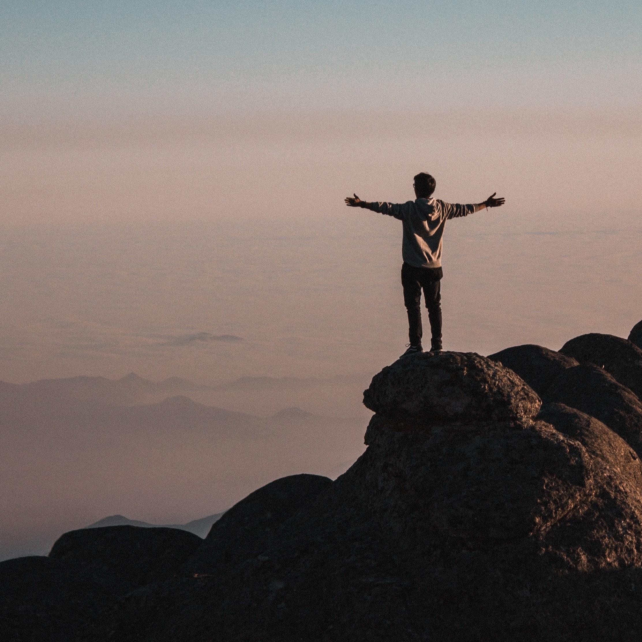 Homem em cima de pedras em uma montanha olhando para o horizonte com os braços abertos.