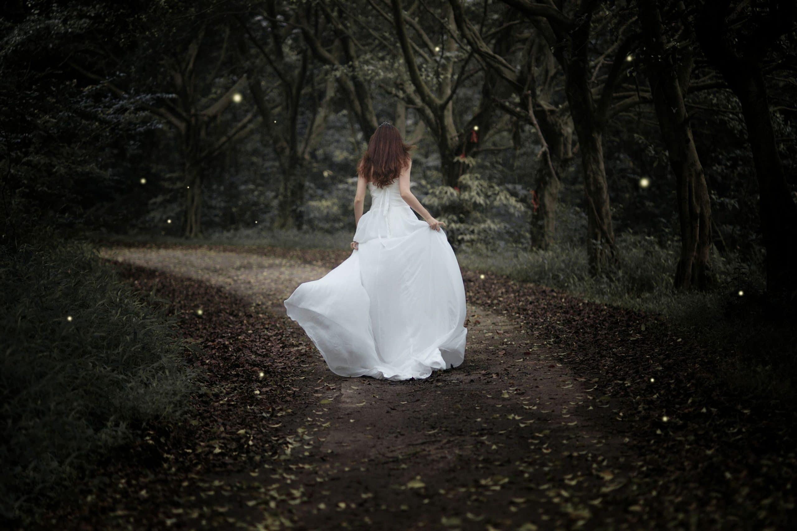 Mulher de vestido branco correndo de costas em floresta com luzes pelo caminho