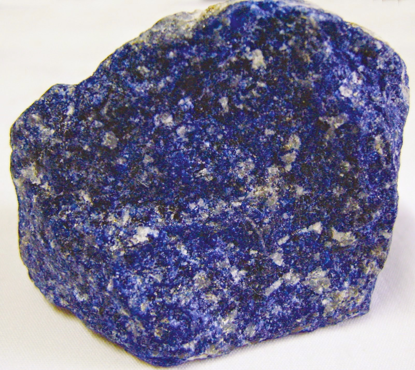 Pedra do cristal pirita azul sobre superfície branca.
