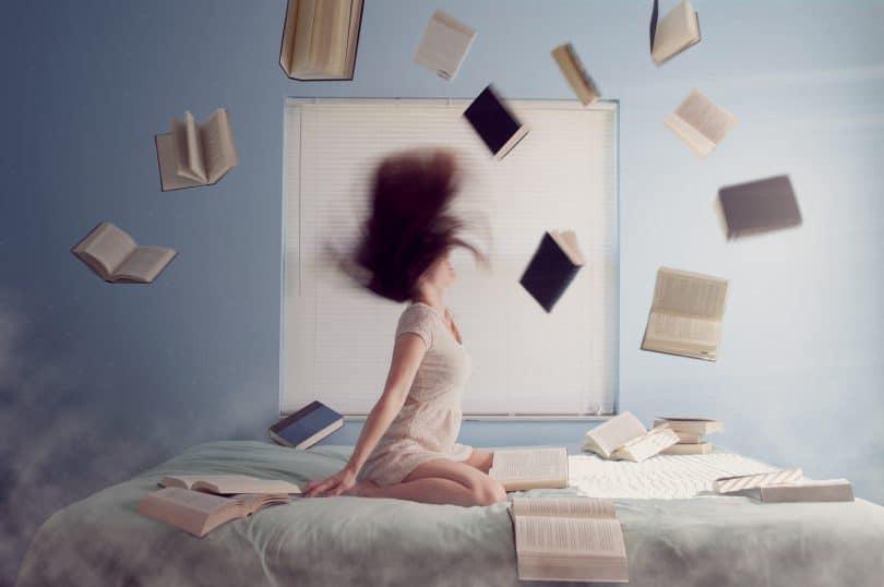 Menina de joelhos na cama jogando cabelo para trás tremida com livros voando