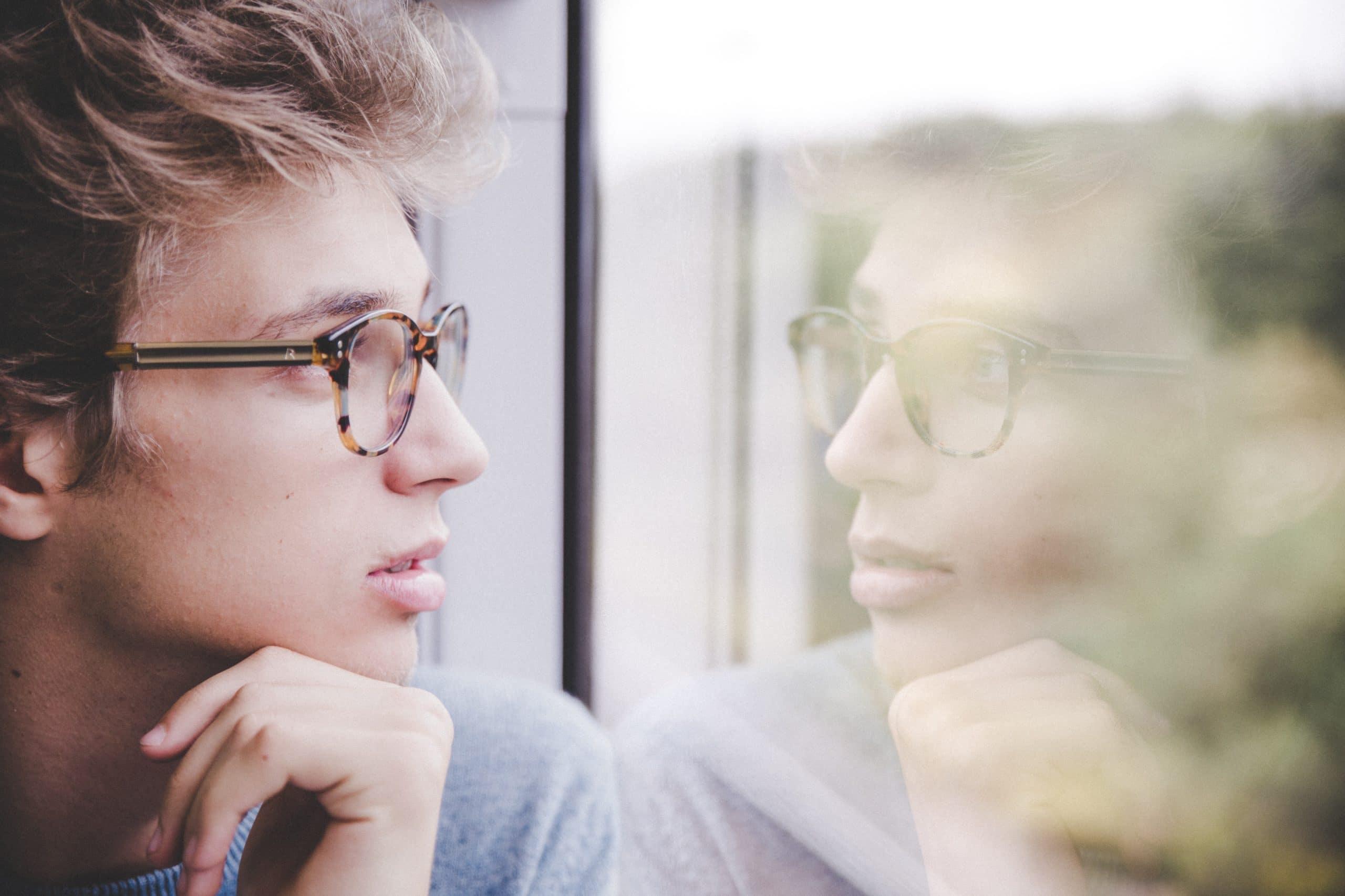 Garoto de cabelo castanho claro e óculos preto encarando seu reflexo em uma janela.