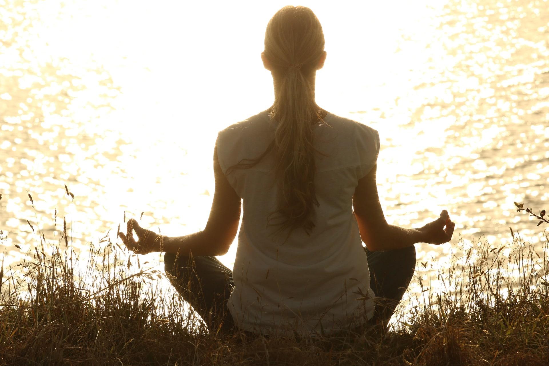 Mulher sentada na grama de frente para um lago com as mãos sobre os joelhos, meditando.