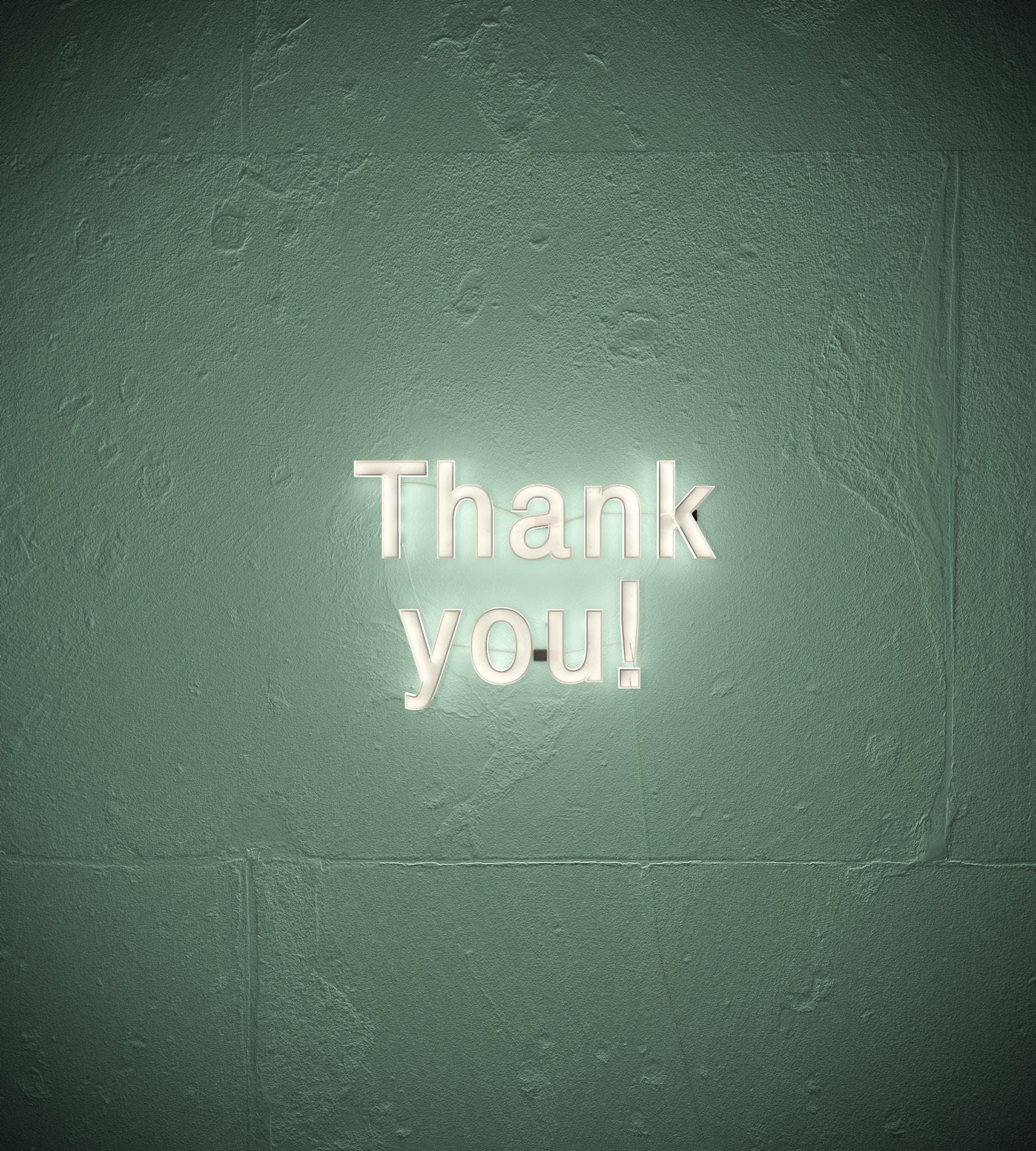 """Letreiro escrito """"Thank you"""" com luz de LED em uma parede verde."""