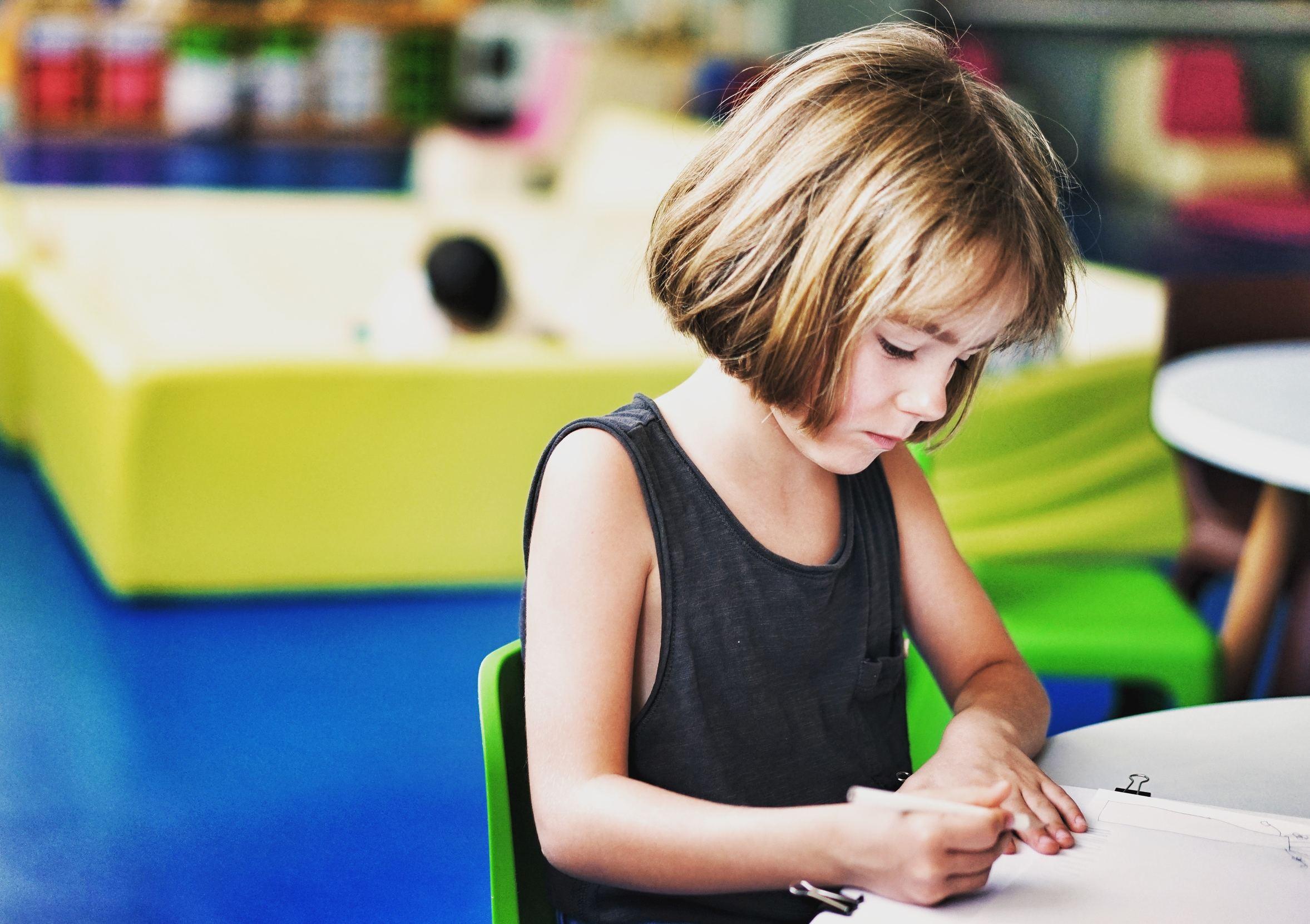 Menina de cabelos curtos no foco sentada em uma mesinha escrevendo