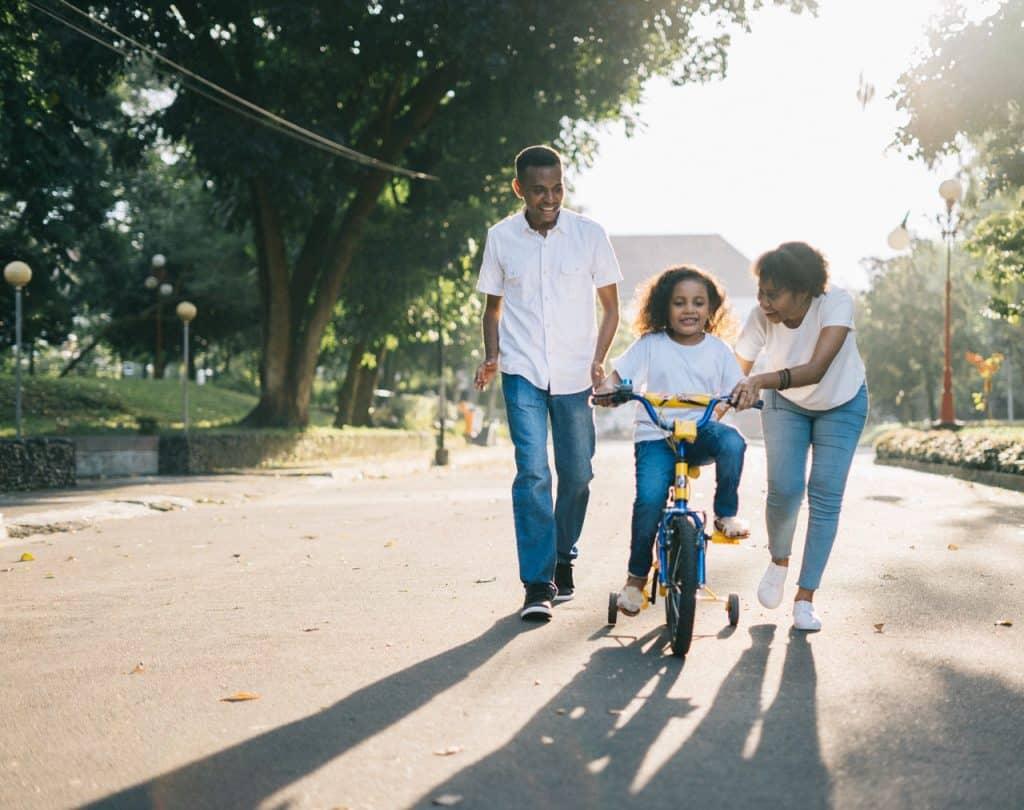 Pai e mãe ajudando sua filha pequena a andar de bicicleta, na rua, durante o dia.