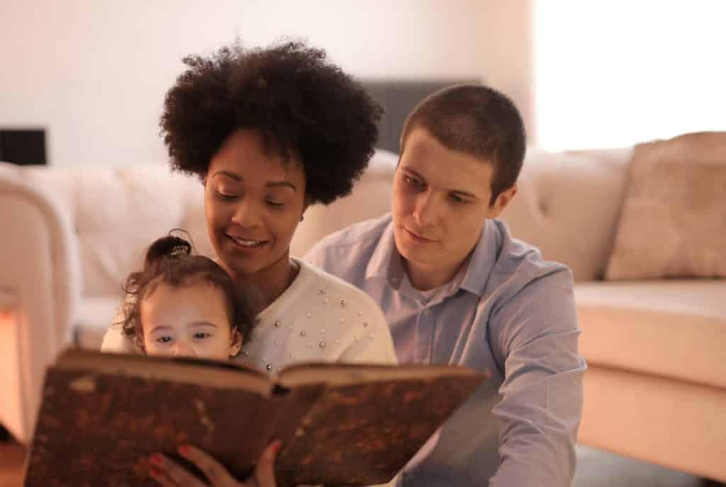 Homem e mulher sentados no chão da sala de estar, lendo um livro para criança pequena.
