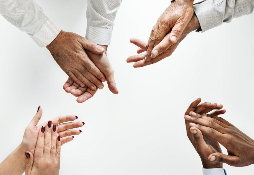 Mãos de 4 pessoas diferentes, todas em posição de aplauso, em frente à um fundo branco.
