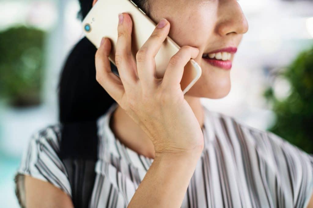 Mulher sorridente, segurando seu celular perto da orelha, como se estivesse falando em uma ligação