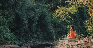 Mulher sentada meditando no meio da natureza.