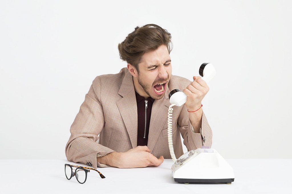 Homem vestindo um terno, sentado em uma mesa branca, gritando para um telefone antigo, branco também.