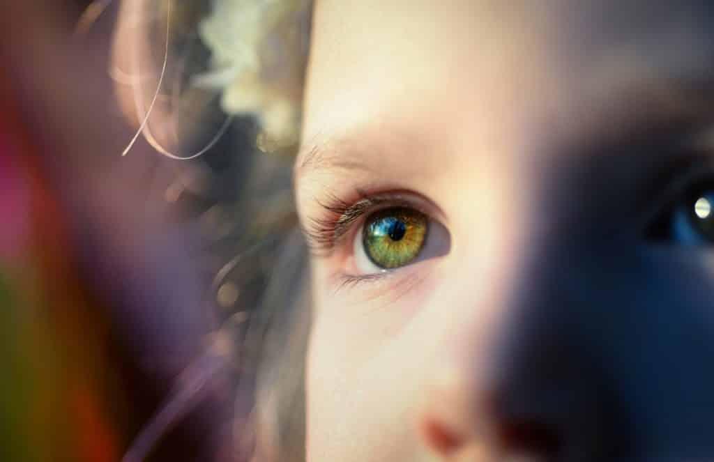 Olhos de uma criança vistos de perto, sob a luz do sol.