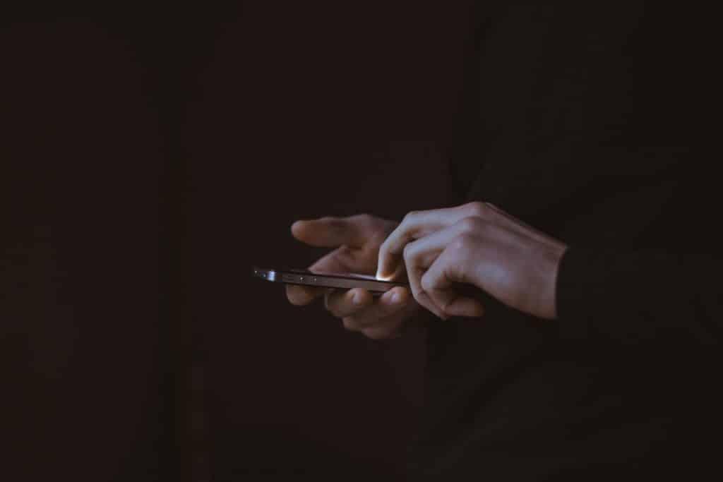 Mãos mexendo em um celular.